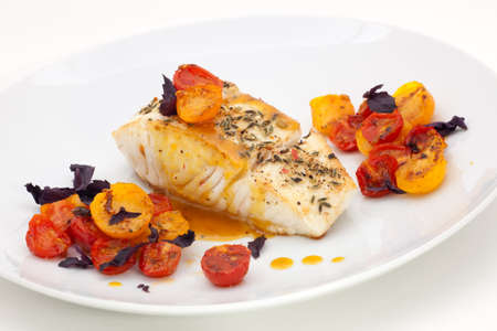 fennel seeds: Pan fried halibut garnished with fennel seeds and spicy mustard sauce, served with fried cherry tomatoes salad with purple basil Stock Photo