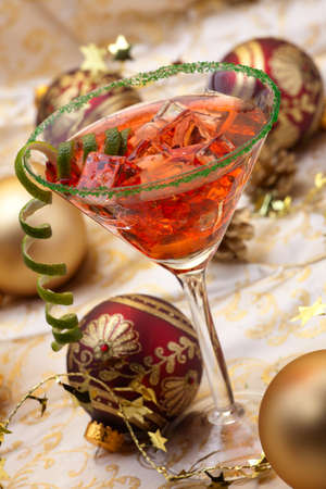 Glass of Christmas Cocktail in martini glass and Christmas ornaments photo