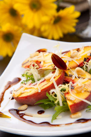 pignons de pin: Gros plan de la salade de p�ches grill� avec fromage Parmesan et pignons grill�s. Sauce balsamique.