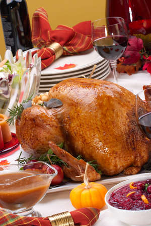 Garnished roasted turkey on holiday decorated table with pumpkins and glasses of red wine Stock Photo - 7800251