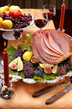 Glazed delicious whole baked honey sliced ham with figs, lemons and champagne grapes. photo