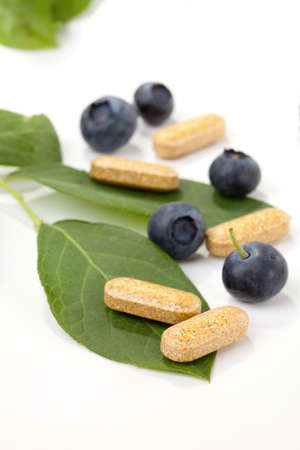 alternative health: Closeup of bilberry extract pills and fresh berries and leaves best suited for alternative medicine ads