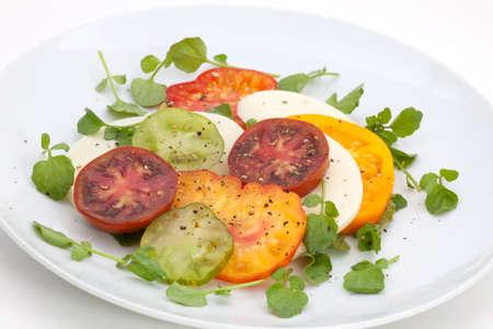 berros: Ensalada de queso de mozzarella con berros y detalle de tomate de la reliquia.  Foto de archivo