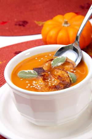 Closeup of a cup of hot delicious spicy roasted pumpkin soup with pumpkin crisps, sage and sesame seads. photo