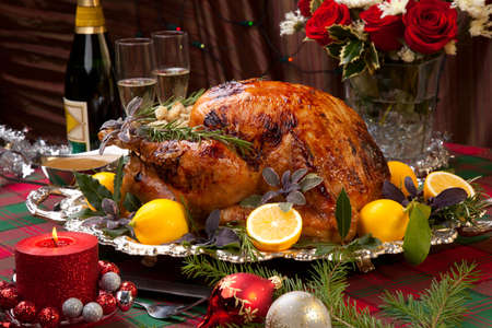 christmas turkey: Garnished roast turkey on Christmas-decorated table with candles and flutes of champagne Stock Photo