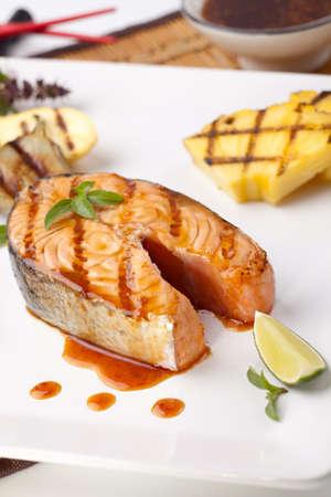 plato de pescado: Delicious a la parrilla teriyaki adornado de filete de salm�n con pi�a a la parrilla, el beb� berenjenas, calabac�n y Chile pepper para cena de estilo sano.