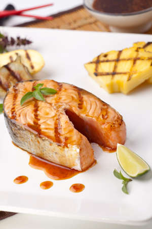 steak plate: Delicious grilled Teriyaki salmon steak garnished with grilled pineapple, baby eggplants, zucchini and chilli pepper for healthy style dinner.