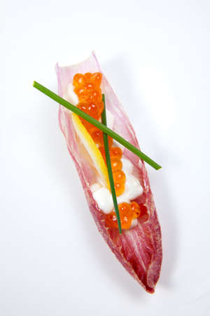 Closeup of red caviar on Creme Fraiche inside red endive leaf canape on white. photo