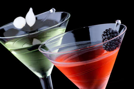 cocktails: Classical martini in chilled glass over black background on reflection surface, garnished with fresh blackberry and marinated pearl onions. Most popular cocktails series. Stock Photo