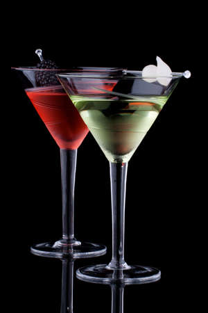 Classical martini in chilled glass over black background on reflection surface, garnished with fresh blackberry and marinated pearl onions. Most popular cocktails series. Stock Photo