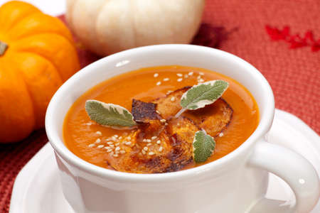 roasted sesame: Closeup of a cup of hot delicious spicy roasted pumpkin soup with pumpkin crisps, sage and sesame seads.