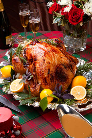 garnished: Garnished roast turkey on Christmas-decorated table with candles and flutes of champagne Stock Photo