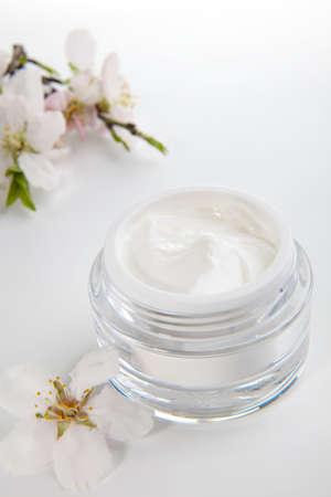 Closeup of jar of moisturizing face cream surrounded by almond flowers Reklamní fotografie