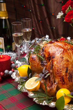 roast turkey: Garnished roast turkey on Christmas-decorated table with candles and flutes of champagne Stock Photo