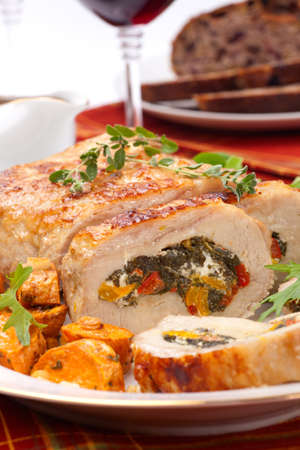 sweet potato: Feta-, spinach-, and bell pepper - stuffed pork tenderloin roulade garnished with sweet potato and green salad.