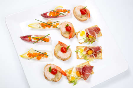 Assorted fresh canapes on tray ready for holiday table over white background Stock Photo - 8466587