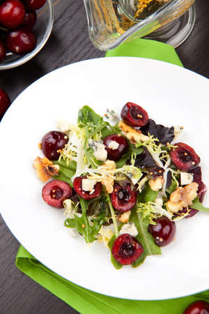 Green salad with cherries, walnuts and blue cheese. Fresh cherries around. Saucer with vinaigrette.