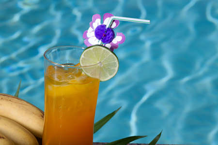 Glass of Mai Tai cocktail on swimming pool side garnished with lime photo