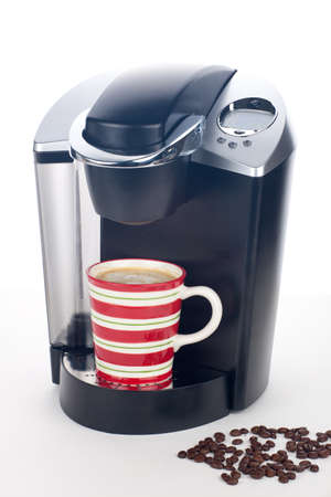 Closeup of expensive coffee maker with mug of fresh brewed coffee and beans around over white Stock Photo - 8628060