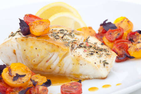 delicious: Pan fried halibut garnished with fennel seeds and spicy mustard sauce, served with fried cherry tomatoes salad with purple basil Stock Photo