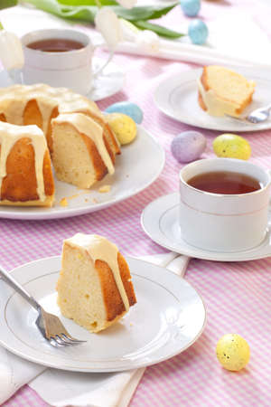 easter cookie: Piece of Lemon Easter cake with lemon icing, served with cup of tea, and decorated with painted eggs Stock Photo