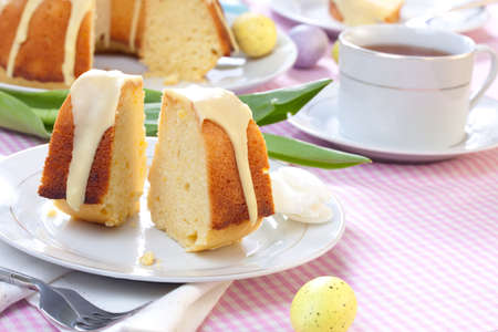 Piece of Lemon Easter cake with lemon icing, served with cup of tea, and decorated with painted eggs Stock Photo