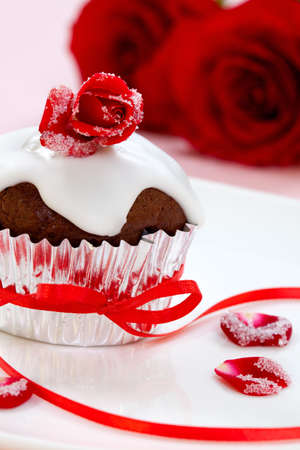 chocolate cupcakes: Chocolate maffin garnished with sugar frosted rose and vanila icing. Valentines day or wedding desert. Stock Photo