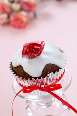 Chocolate maffin garnished with sugar frosted rose and vanila icing. Valentines day or wedding desert. photo