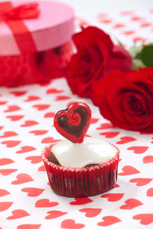 Closeup of Valentine day chocolate cupcakes garnished with heart shaped chocolates. Red roses and gift in background. photo