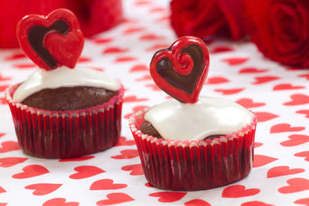 Closeup of Valentine day chocolate cupcakes garnished with heart shaped chocolates. Red roses and gift in background. Banco de Imagens