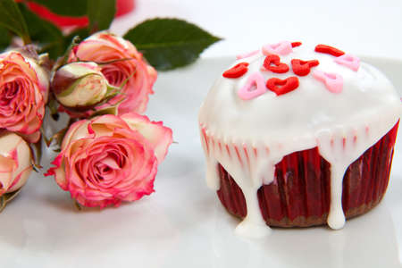Valentine day chocolate cupcakes garnished with heart shaped sprinkles. Pink roses and gift in background. photo