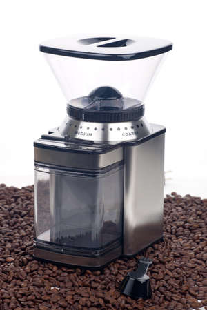 Closeup of modern coffee grinder with coffee beans around over white Stock Photo - 8714056