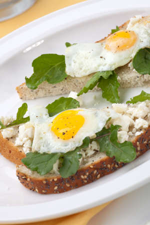 Closeup of delicious open-face sandwiches with feta cheese, arugula, and fried quail eggs. photo