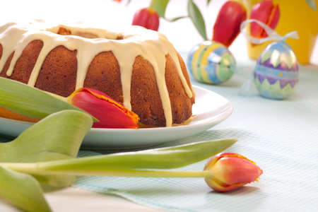 Easter cake with lemon icing, decorated with painted eggs and fresh tulips  photo