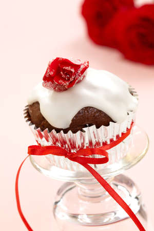 Chocolate muffin garnished with sugar frosted rose and vanilla icing. Valentine's day or wedding desert. Stock Photo - 8804774