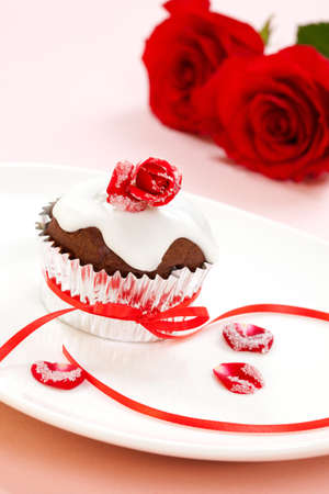Chocolate muffin garnished with sugar frosted rose and vanilla icing. Valentines day or wedding desert. photo