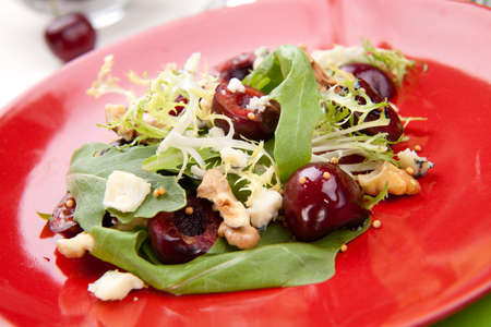 Green salad with cherries, walnuts and blue cheese. Fresh cherries around. Saucer with vinaigrette. photo