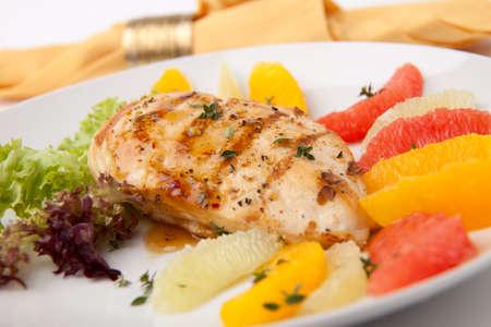 Pechuga de pollo a la plancha con ensalada de cítrico - pomelo rosa, limón, naranja, lechuga y tomillo fresco. Foto de archivo - 8804804