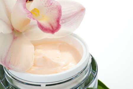 Closeup of jar of face cream and blooming light pink Cymbidium orchid flower Reklamní fotografie