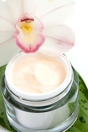 Closeup del vasetto di crema per il viso e rigogliosa luce rosa fiori di orchidea del Cymbidium Archivio Fotografico - 8927847