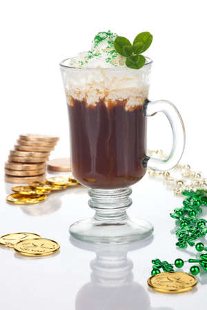 Mug of Irish Coffee with green sprinkles and clover leaf surrounded with gold coins and shamrock ornament for St Patick's Day Stock Photo - 8927841