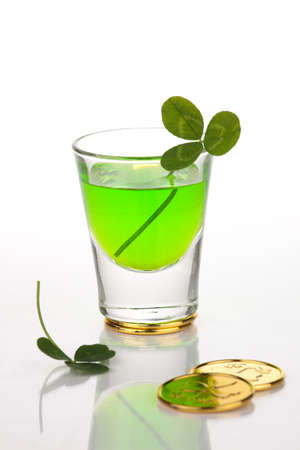 Shot of green liquor for St Patricks Day surrounded with gold coins and clover leaf. photo