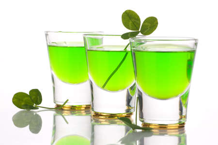 Row of green liquor shots for St Patricks Day and clover leafs.