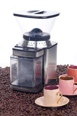 Closeup of modern coffee grinder with coffee beans around over white Stock Photo - 8999710