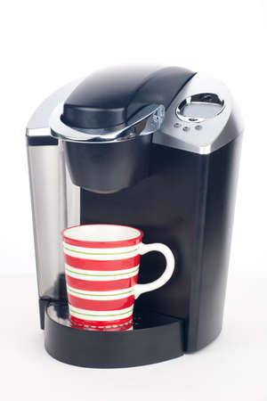 Closeup of expensive coffee maker with mug of fresh brewed coffee and beans around over white Stock Photo - 8999708
