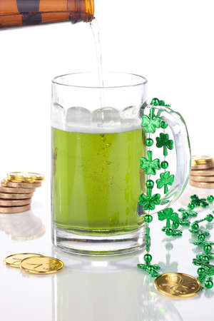 Mug of green beer for St Patricks Day surrounded with gold coins and shamrock ornament photo