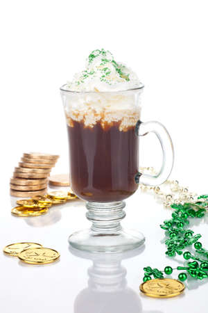 Mug of Irish Coffee with green sprinkles and clover leaf surrounded with gold coins and shamrock ornament for St Patrick's Day Stock Photo - 8999711