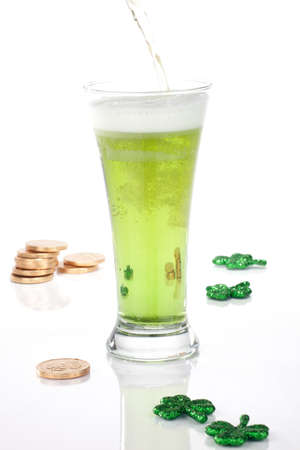 Glass of green beer for St Patricks Day surrounded with gold coins and shamrock ornament photo