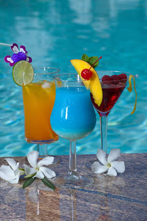 Mai Tai, Blue Hawaiian, and Cosmopolitan cocktails on swimming pool side photo