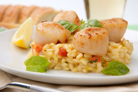 Plate of Scallops Risotto garnished with fresh basil, glass of white wine and bread. Stock Photo